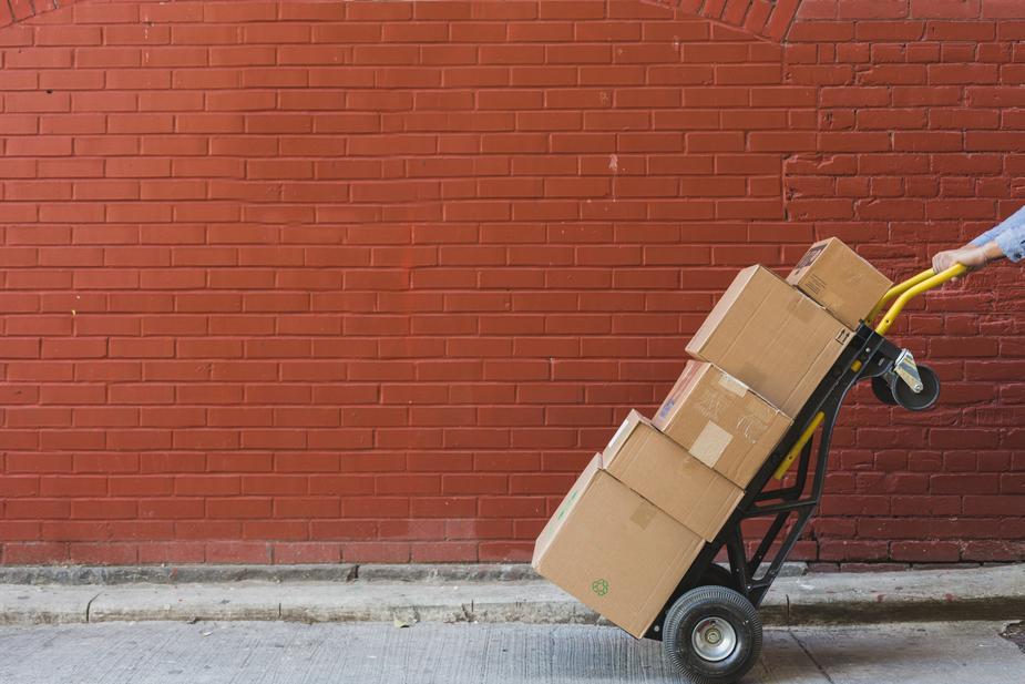 paczki na wózku dostarczane przez kuriera