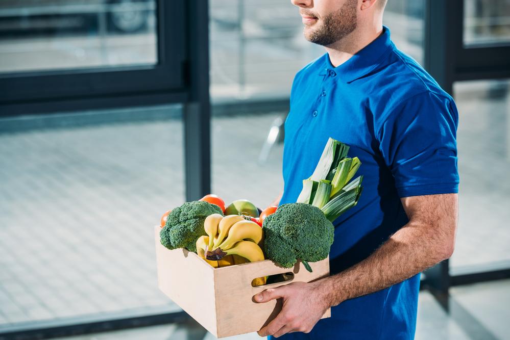 Kurier z paczka z żywnością, e-gorcery, zakupy spożywcze